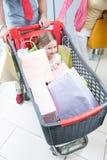 Primo piano di giovane figlia in carrello che è spinto dal padre e madre Fotografia Stock Libera da Diritti