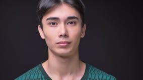 Primo piano di giovane fronte maschio coreano attraente con gli occhi marroni che esaminano diritto la macchina fotografica video d archivio