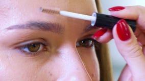 Primo piano di giovane fronte di modello femminile che ottiene correzione professionale di forma del sopracciglio al salone di be video d archivio