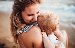 Primo piano di giovane madre con una ragazza del bambino sulla spiaggia sulla vacanza estiva fotografia stock libera da diritti