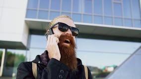 Primo piano di giovane uomo barbuto dei pantaloni a vita bassa in occhiali da sole che sorride e che parla smartphone vicino agli fotografia stock