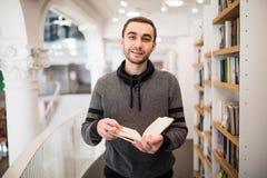 Primo piano di giovane uomo caucasico con gli occhiali in una libreria con un libro aperto in sue mani che legge qualcosa con alt Immagini Stock
