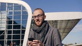 Primo piano di giovane uomo d'affari in vetri che sta camminando sulle vie urbane, facendo uso dello Smart Phone moderno - tutto  stock footage