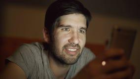 Primo piano di giovane uomo sorridente che per mezzo dello smartphone per praticare il surfing media sociali che si trovano a let video d archivio