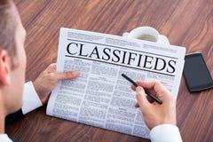 Primo piano di giovani classifieds della lettura dell'uomo d'affari immagini stock libere da diritti