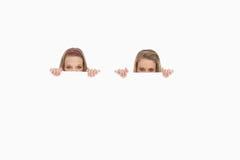 Primo piano di giovani donne che si nascondono dietro un segno in bianco Immagine Stock