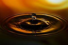 Primo piano di goccia di acqua su fondo giallo arancione Fotografie Stock Libere da Diritti
