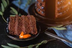 Primo piano di grande pezzo di dolce di cioccolato delizioso con le bacche su un fondo nero fotografia stock libera da diritti