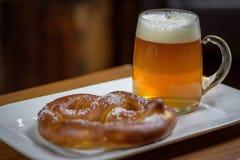 Primo piano di grande tazza di vetro di birra e di una ciambellina salata molle immagini stock