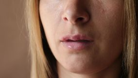 Primo piano di herpes delle ulcere del labbro del ` s delle donne Le belle labbra sono state coperte di febbri La ragazza lecca l video d archivio