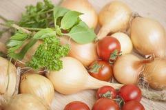 Primo piano di intere cipolle del rendimento ecologico di autunno, pomodori ciliegia e basilico e prezzemolo freschi al sole Fotografia Stock Libera da Diritti