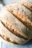 Primo piano di intero pane del grano su un asciugamano di cucina grigio Immagini Stock