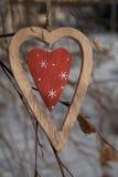 Primo piano di legno alla moda del cuore su un ramo nell'inverno Immagine Stock Libera da Diritti
