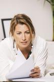 Primo piano di lettura della donna di affari maturi documenti nel letto. Immagine Stock