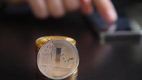 Primo piano di Litecoin del sistema di pagamento cripto-virtuale del ` s del mondo Smartphone, leggente le notizie finanziarie su video d archivio
