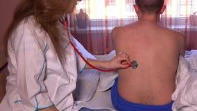Primo piano di medico femminile che per mezzo dello stetoscopio per controllare respirazione del paziente archivi video