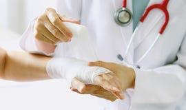 Primo piano di medico femminile con lo stetoscopio che benda mano del paziente fotografia stock libera da diritti