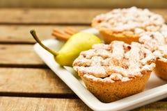 Primo piano di mini torte su un piatto decorato con cannella e una pera Fotografia Stock Libera da Diritti