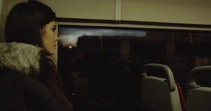 Primo piano di modello splendido che fantastica su un bus Una giovane donna guarda fuori la finestra sul bus 4K stock footage