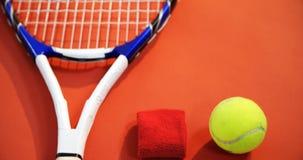 Primo piano di pallina da tennis, della banda di polso e della racchetta sul pavimento rosso 4k archivi video