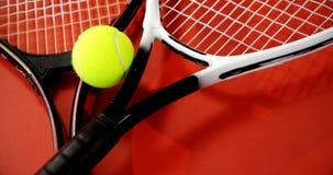 Primo piano di pallina da tennis e delle racchette sul pavimento rosso 4k video d archivio