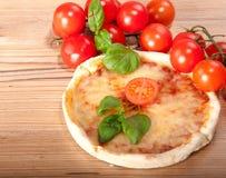 Primo piano di pizza con i pomodori, il formaggio ed il basilico su fondo di legno Fotografie Stock Libere da Diritti