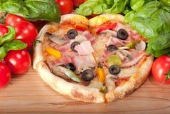 Primo piano di pizza con i pomodori, il formaggio ed il basilico su fondo di legno Immagine Stock