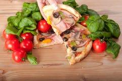 Primo piano di pizza con il handsl dei pomodori, del formaggio, di basi e della donna su fondo di legno Fotografia Stock Libera da Diritti