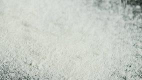 Primo piano di polvere bianca che si rovescia sul fondo nero Metraggio di riserva La polvere bianca della cocaina è sparsa sul ne archivi video