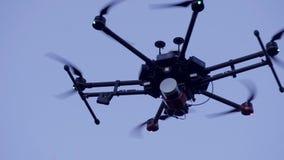 Primo piano di quadcopter che vola in cielo clip Grande quadcopter con i motori potenti che volano sul cielo blu del fondo video d archivio
