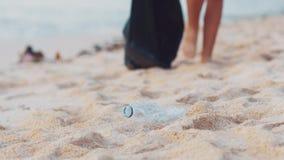 Primo piano di raccolto della bottiglia di plastica volontaria su sulla spiaggia bianca dell'oceano Volontario che pulisce la spi archivi video