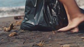 Primo piano di raccolto della bottiglia di plastica volontaria su sulla spiaggia di sabbia nera nel sacchetto di plastica nero Pu stock footage