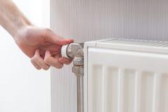 Primo piano di registrazione del radiatore Mano del ` s dell'uomo che regola temperatura del radiatore fotografia stock