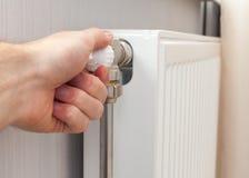 Primo piano di registrazione del radiatore Mano del ` s dell'uomo che regola temperatura del radiatore immagini stock libere da diritti