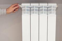 Primo piano di registrazione del radiatore Mano del ` s della donna che regola temperatura del radiatore fotografie stock
