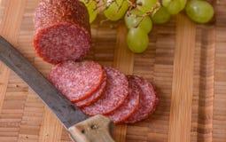 Primo piano di salame con un coltello e qualche uva dal lato Fotografia Stock