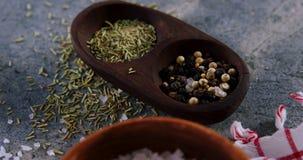 Primo piano di sale, dello speice, del pepe nero, dell'aglio e delle erbe stock footage