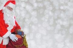 Primo piano di Santa Claus con la sua borsa dei giocattoli sopra un bokeh d'argento fotografia stock