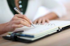 Primo piano di scrittura della mano della donna nell'ordine del giorno Fotografia Stock