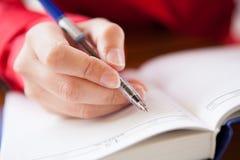 Primo piano di scrittura della mano in diario Fotografia Stock