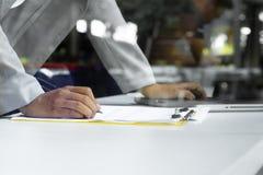 Primo piano di scrittura umana della mano su una carta Fotografia Stock Libera da Diritti
