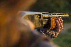 Primo piano di signora che tende fucile da caccia Immagine Stock