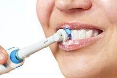 Primo piano di spazzolatura dello spazzolino da denti elettrico dei denti della donna isolato immagine stock
