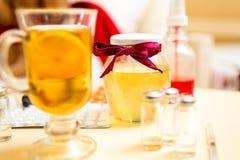 Primo piano di tè, del barattolo del miele e delle pillole caldi sul comodino Fotografie Stock
