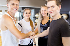 Primo piano di tenersi per mano allegro del gruppo di allenamento di forma fisica Immagine Stock