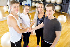 Primo piano di tenersi per mano allegro del gruppo di allenamento di forma fisica Fotografie Stock