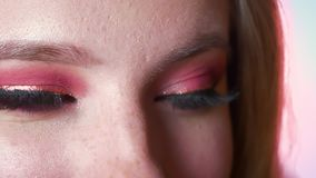 Primo piano di trucco femminile sbalorditivo degli occhi azzurri con le tonalità e il eyeline rosa dell'oro Vista laterale Occhi  video d archivio