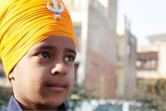 Primo piano di un bambino sikh con il turbante dello zafferano Immagini Stock Libere da Diritti