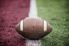 Primo piano di un calcio che si siede sulla linea di fondo ad uno stadio di football americano fotografie stock