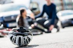 Primo piano di un casco andante in bicicletta caduto giù sulla terra dopo la a fotografie stock